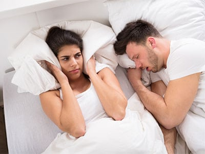 woman trying to sleep with loud snoring husband